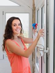 Happy woman washing windows in house