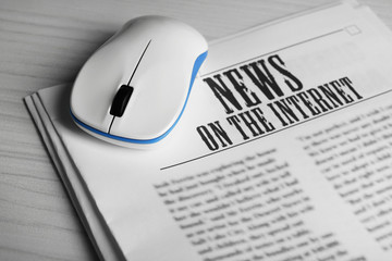 On-line news concept. Computer mouse and newspaper