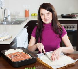Smiling girl cooking fish pie