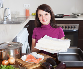 Smiling girl cooking fish pie with  store-bought dough