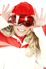 Happy female snowboarder playing with her goggles.