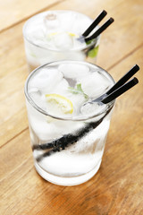 Glass of water with ice cubes and lemon on wooden table