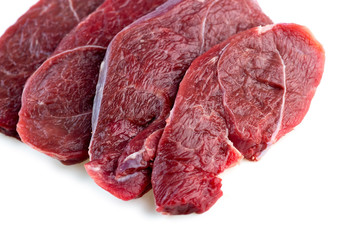 Studio shot of raw red meat steaks isolated against a white back