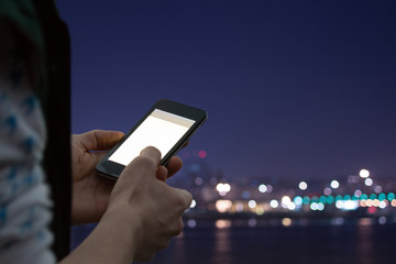Typing messages  - with defocused city lights.