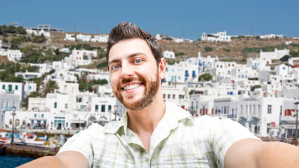 Happy young man taking a selfie photo in Greece
