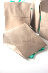 small gift wrapped in recycled paper with ribbon bow, isolated