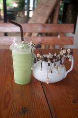 Milk Green tea smoothie in plastic cup on wood table