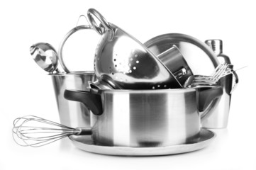 Stainless steel kitchenware on table, isolated on white