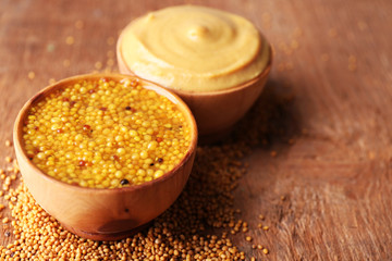 Mustard in bowls on wooden background