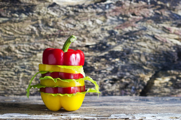 colorful sweet pepper slices decoration on wooden background, bl
