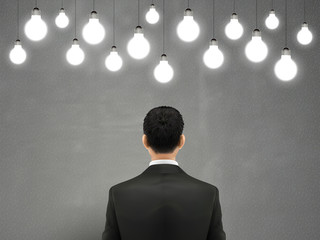 businessman with hanging lighting bulbs