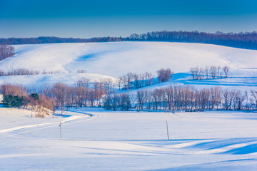 View of snow covered rolling hills and farm fields in rural York