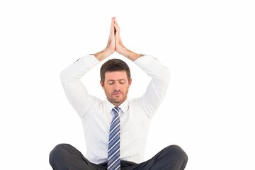 Businessman meditating in lotus pose