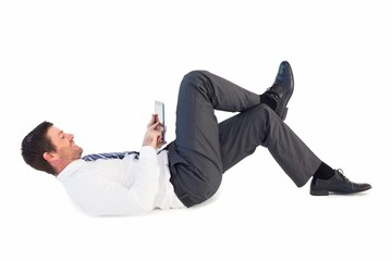 Businessman lying and using tablet