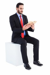 Thoughtful businessman sitting reading book