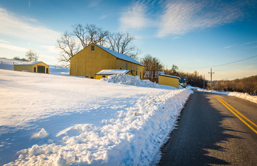 Yellow barn and a snow covered field along a country road in Yor