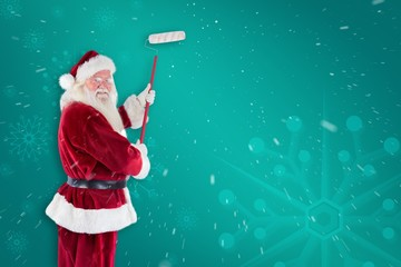 Composite image of father christmas paints a wall