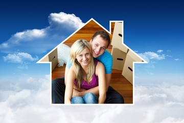 Composite image of house frame in couple sitting on floor