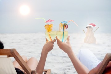 Composite image of couple clinking glasses of cocktail on beach