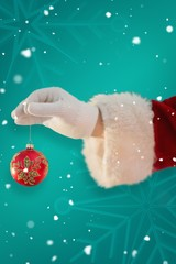 Composite image of santas hand is holding a christmas bulb