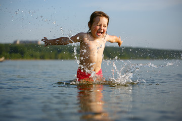 Little girl laughing and crying in the spray of waves at sea