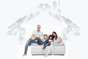 Composite image of family sitting on sofa smiling at camera