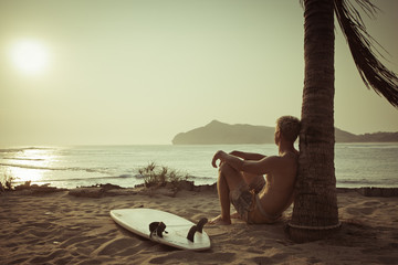 Old photo of surfer near the palm