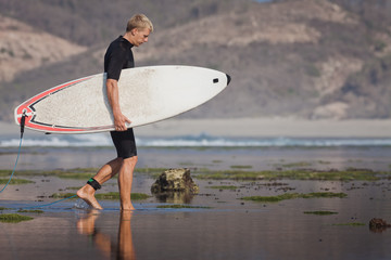 Surfer with surfboard on the beach
