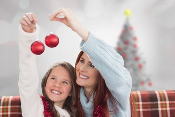 Composite image of mother and daughter holding baubles