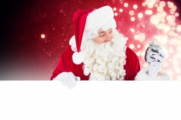 Composite image of happy santa holding alarm clock and sign
