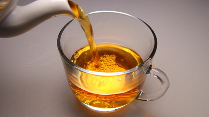 Pouring tea into the cup and stir sugar