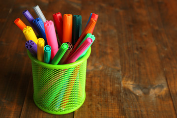 Colorful markers in metal holder on rustic wooden background