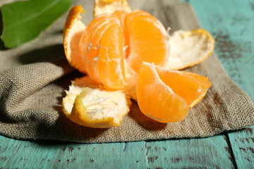 Juicy ripe tangerine with leaves on wooden table