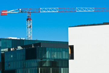Building crane and building under constrction against blue sky