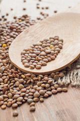Organic lentils with wooden false on burlap background