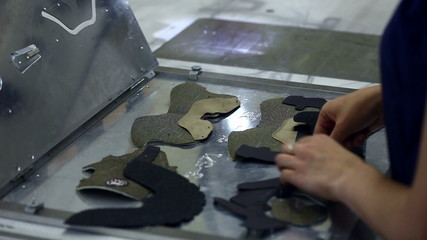 Worker puts stitched parts for production of boots