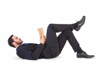 Businessman lying on the floor reading a book