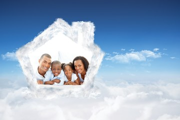 Composite image of happy family having fun lying down on bed