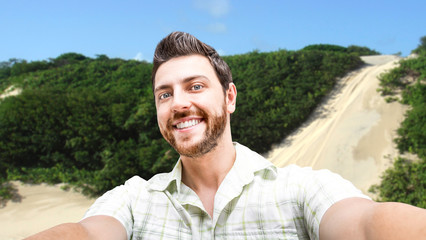 Happy young man taking a selfie photo in Natal, Brazil