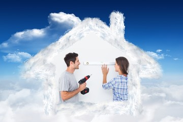 Composite image of man and his wife doing diy together