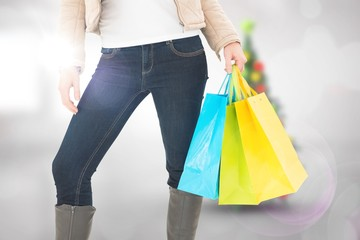 Composite image of mid section of woman holding shopping bags