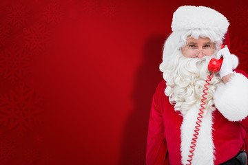 Composite image of smiling santa claus on the phone
