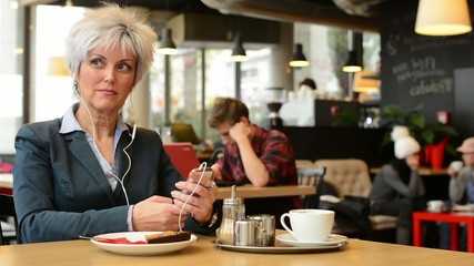 middle aged woman listens music in cafe (earphone) on smartphone