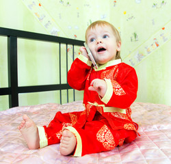 Funny little boy calls the room service in hotel by his telephon