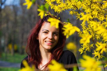 Young woman between yellow flowers