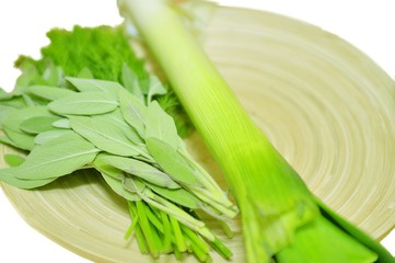 Wooden plate with leek and mint isolated