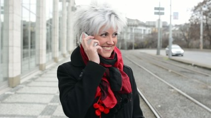 middle aged woman phones with smartphone - urban street