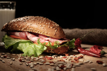 Sandwich on a wooden table with slices of bacon, lettuce and tom