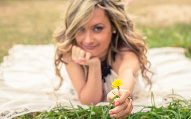 Romantic girl holding flower in the hand lying down outdoors