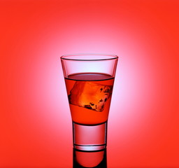 Short drink glass with red liquid and ice cubes